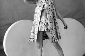 Black and white fashion photo of a woman in a 2-piece bathing suit and cover-up.