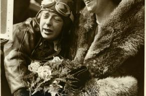 Black and white photograph of a woman in a pilot's gear hugging a woman holding flowers.