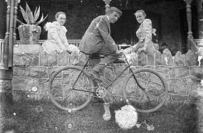 Black and white negative photograph of a man on a bike, flanked by two women sitting on a wall.