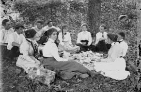 Black and white glass negative showing a group of young men and women having a picnic in the woods. An older man, artist Howard Pyle, is also present.