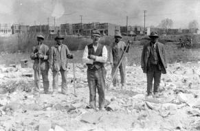 Black and white image of workmen on a cleared construction site.