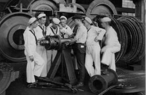 Black and white image of cadets dressed in nautical uniforms examining large machinery in a factory..