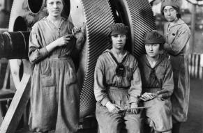 Black and white photograph of four women in work clothes, standing in front of large industrial gears.