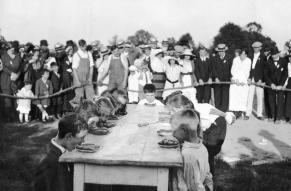 Black and white image of children lined up at a table, in front of an audience, for a pie eating contest.