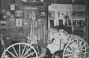 Black and white image of a man in a coat and top hat, seated in a booth exhibiting the works of the Hoopes Brothers & Darlington company.
