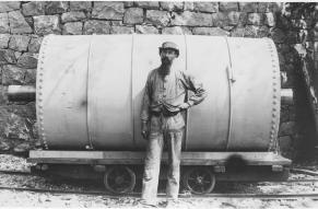 Black and white image of a bearded person standing in front of an industrial glazing barrel.