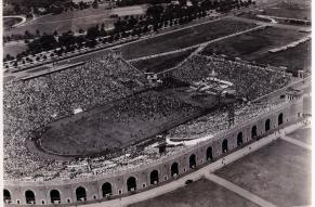Black and white aerial photograph of an open-air stadium full of people