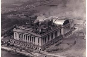 Black and white aerial photograph of a large electric plant located along a river.