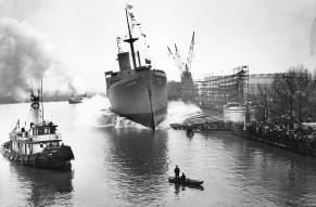 Black and white image of a large freighter ship being dropped into a busy river with many ships.