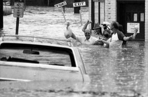 Black and white photograph of a group of men wading through heavily flooded streets.