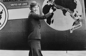 Black and white photograph of a woman in a stewardess uniform standing in front of a decorated airplane body. Plane body shows a globe with directional markers running from London to Melbourne.