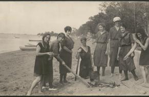 Panoramic black and white photograph of a group of women on a beach assembling a bonfire.