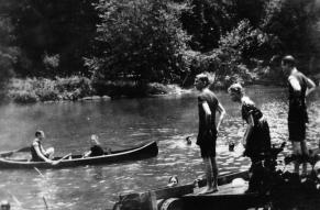 Black and white photograph of people canoeing and swimming in what is probably the Brandywine River.