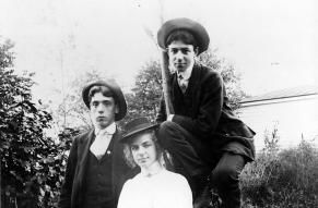 Black and white image of three young people in their late teens; two young men and a woman.