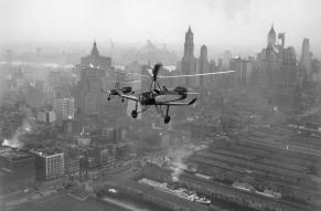 Black and white image of two autogyros flying over a cityscape.