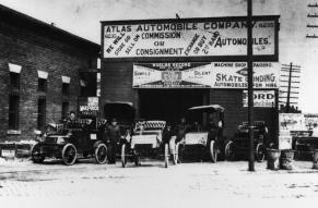 Black and white photograph of cars and staff outside of an early 20th century automobile dealership and service station.