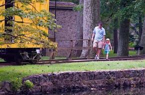 A man and young girl walk at Hagley