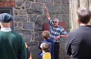 A Hagley guide talks to a tour about a building composed of stone.
