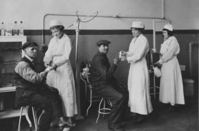 Black and white photograph of nurses and patients in machine shop dispensary.