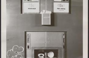 Close up black and white photograph of a food vending machine offering potato salad and fruit cocktail in cherry jello.