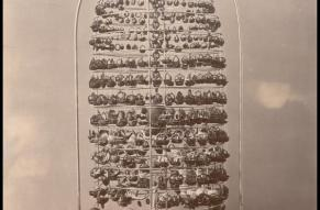 Black and white photo of a bell jar display containing a large number of small ornaments carved from nutshells.