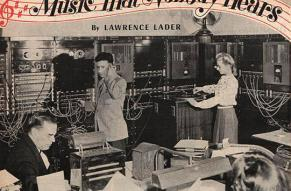 Photo of two men and a woman in a room full of large electronic equipment.